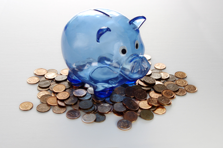 Blue transparent piggy bank on pennies