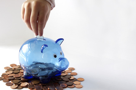 Child`s hand putting money in blue transparent piggy bank on pennies with copy space Stock Photo