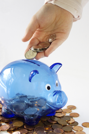 Child`s hand putting money in blue transparent piggy bank on pennies