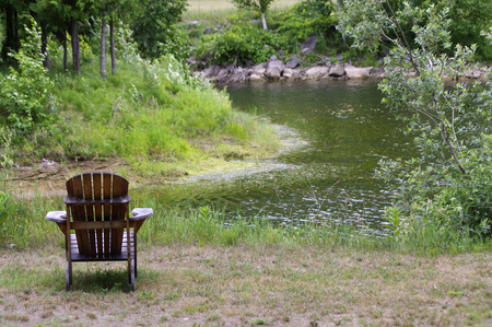 Adirondack chair looking over pond in summer Stock Photo