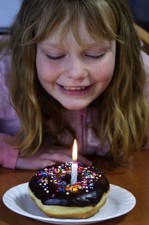 Young Girl looking down at chocolate dipped donut with sprinkles with birthday candle