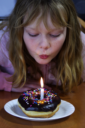 Young Girl blowing out candle in chocolate dipped donut with sprinkles