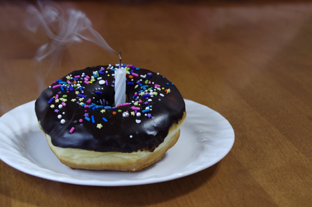 Chocolate dipped donut with sprinkles with birthday candle and smoke Stock Photo