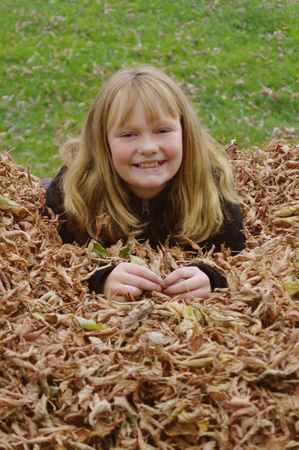 Young girl in fall leaves Stock Photo