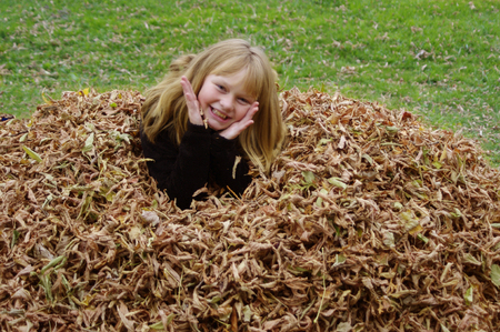 Girl in fall leave pile