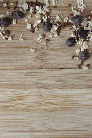 Oats, flax seeds and chocolate chips  seeds on wooden table with copy space
