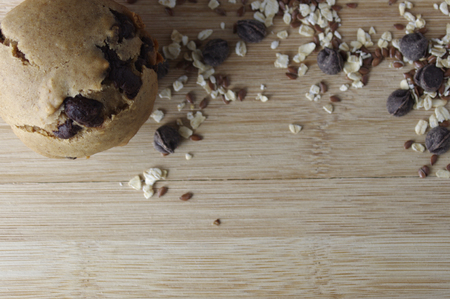Homemade muffins on wooden table with oats and seeds