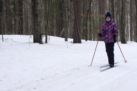 Teenage Girl cross-country skiing in woods