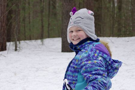 Girl cross-country skiing in woods
