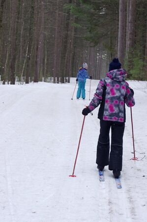 Girl cross-country skiing in woods while it snows