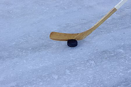 wooden hockey stick with puck on white ice with copy space 写真素材