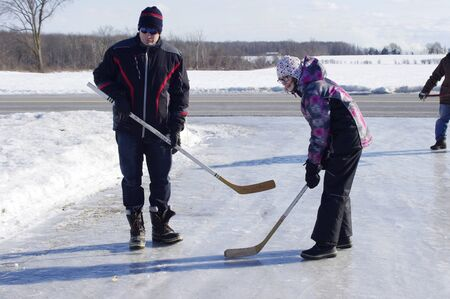 hockey face off between father and daughter on icy driveway in country Stock fotó