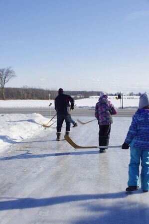 family hockey game on icy driveway in country