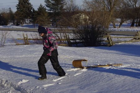 girl pulling toboggan in front yard Banque d'images
