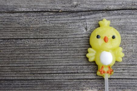 One candy lollipop chick on a rustic wooden background with copy space 写真素材