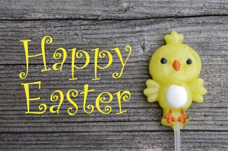One candy lollipop chick on a rustic wooden background with Happy Easter
