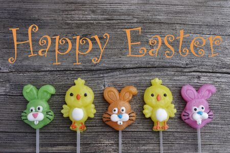 Candy lollipop chicks and bunnies on a rustic wooden background with Happy Easter words Stok Fotoğraf - 140237123