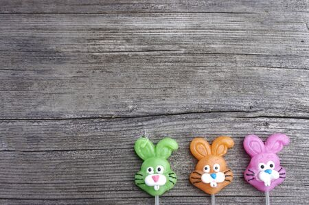 Three candy lollipop bunnies on a rustic wooden background with copy space Stok Fotoğraf - 140545063