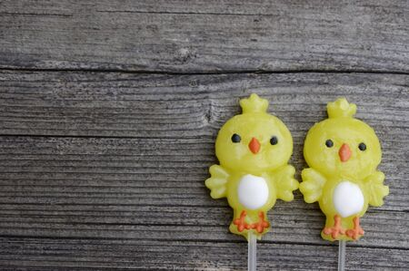 Two candy lollipop chicks on a rustic wooden background with copy space 写真素材
