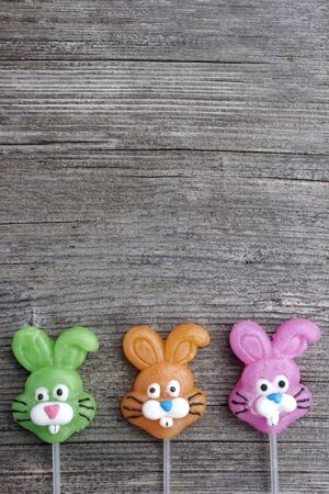 Three candy lollipop bunnies on a rustic wooden Stok Fotoğraf - 140598775
