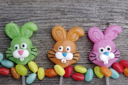Three candy lollipop bunnies on a rustic wooden background with copy space Stok Fotoğraf - 138941341