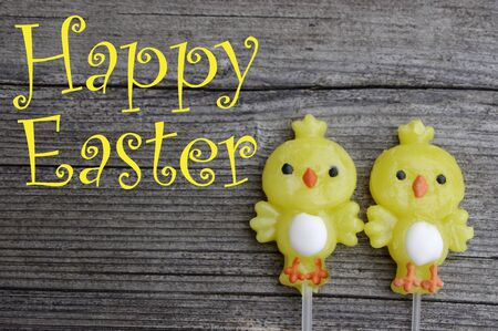Two candy lollipop chicks on a rustic wooden background with Happy Easter