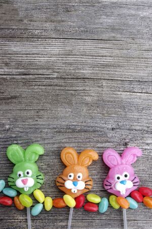 Three candy lollipop bunnies on a rustic wooden background with copy space