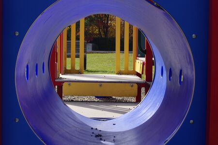 playground viewed from inside blue plastic tunnel Stok Fotoğraf