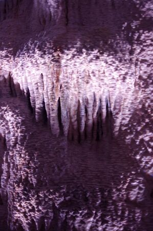 rock stalactites on rock wall in dark tunnel Stok Fotoğraf - 144142461
