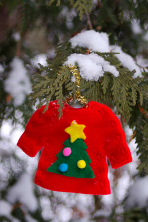 ugly Christmas sweater ornament hanging in snow covered tree with copy space