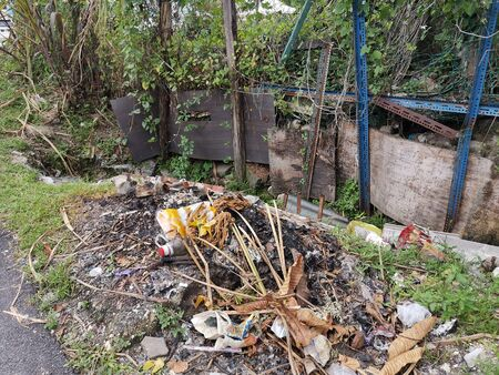 Illegal waste dumped in the nature, in countryside street; environmental and social issue, causing environmental pollution, waste management
