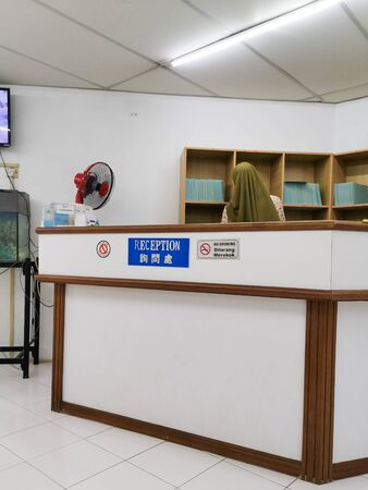Traditional clinic reception with unidentifiable lady receptionist searching for medical records