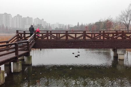 Suwon, A father and daughter watching first snow together at the small wooden bridge on a lake, South Korea