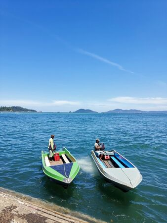 Two men waiting at the speedboats on the blue sea on sunny day for island hopping 新聞圖片