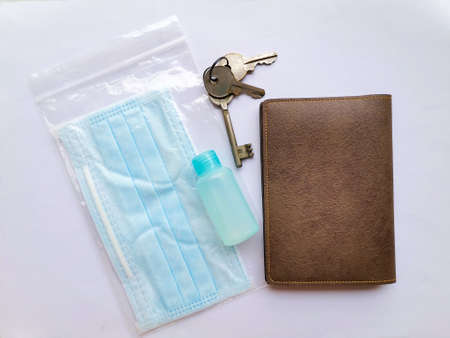 Face mask, sanitizer, keys and wallet, items to carry in Covid 19 ready carry on bag