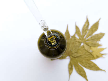 Draw liquid oil out with pipette from bottle on leaves white background