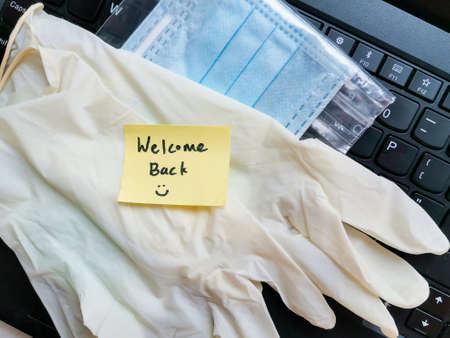 Welcome back message with glove and mask on keyboard to prevent coronavirus, back to work greeting with ppe mask and glove