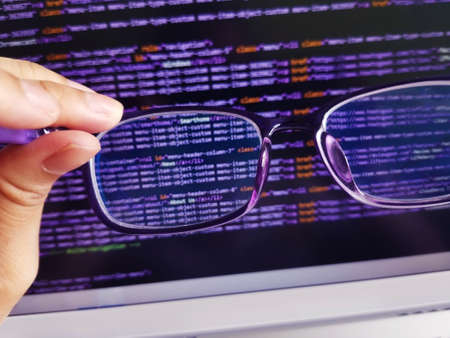 Coding programming language on the screen. Hand holding eye glasses technology showing coding on screen