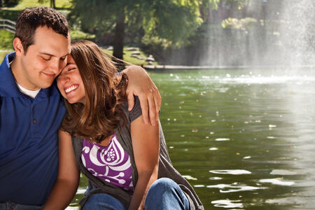 Couple laughing and having fun by lake photo