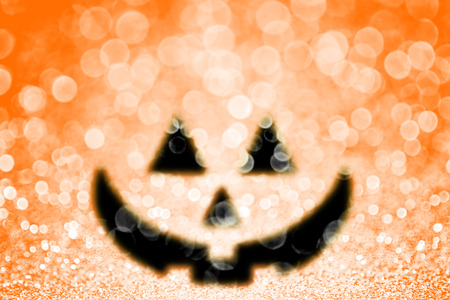 Abstract happy Halloween orange pumpkin jack o lantern glitter sparkle background or trick or treat party invite 版權商用圖片