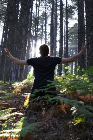 Man Kneeling in the forest with arms lifted up