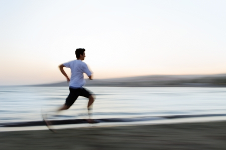Man jogging on the beach with motion blur