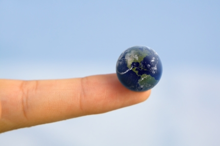 Earth on human finger Stock Photo