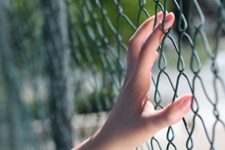 Hand on fence Stock Photo