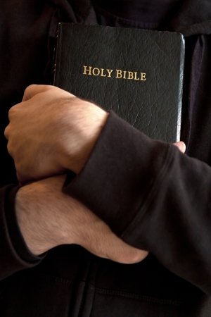 Young man holding a Bible closely