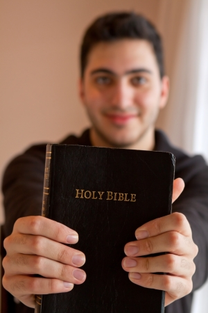 Young man proudly showing his Bible