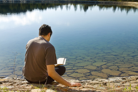 Man reading Book by lake Stock Photo - 64575367