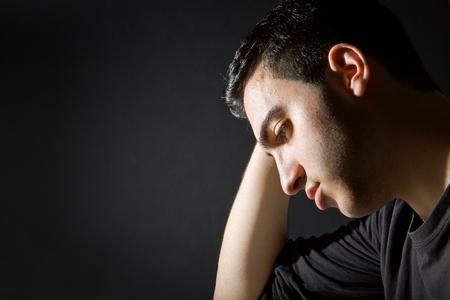 Man thinking on black background, low key