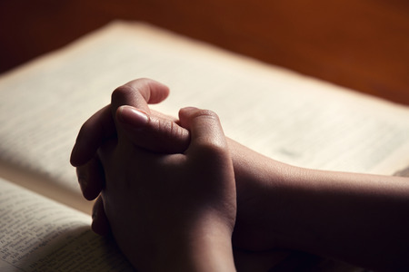 Female hands on Bible Stock Photo