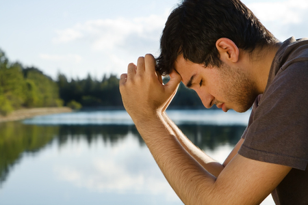 Man Praying by Lake Stock Photo - 64575374